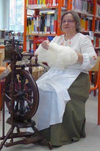 mit dem Spinnrad in einer Schulbibliothek